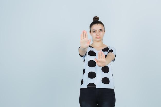 티셔츠, 청바지에 정지 제스처를 보여주는 젊은 아가씨의 초상화와 심각한 전면보기를 찾고