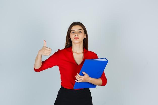 赤いブラウスでフォルダーを保持しながら親指を表示する若い女性の肖像画