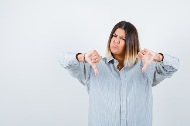 Портрет молодой женщины, показывающей большие пальцы вниз в рубашке оверсайз и недовольной, вид спереди