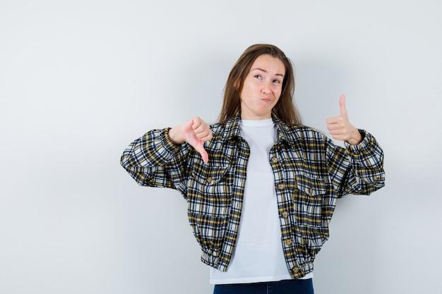 Tシャツ、ジャケット、躊躇している正面図で親指を上下に示す若い女性の肖像画