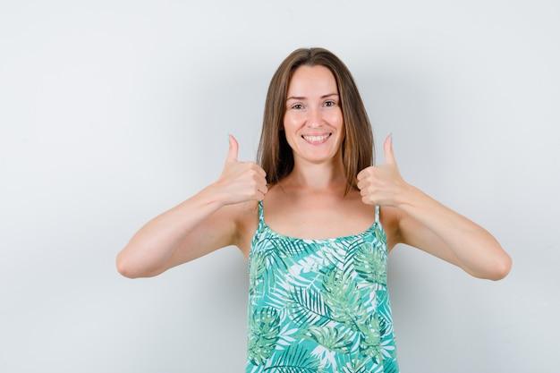 親指を立てて幸せな正面図を見て若い女性の肖像画