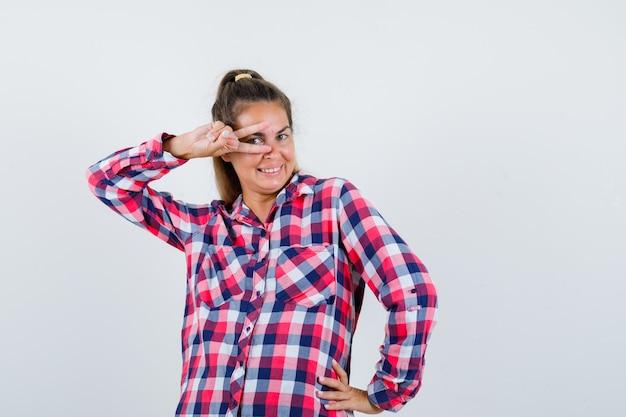 チェックのシャツと幸せな正面図を見て目にvサインを示す若い女性の肖像画