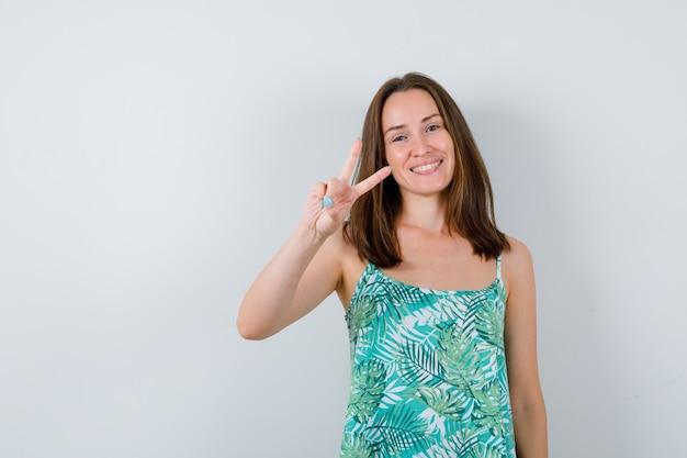 勝利のジェスチャーを示し、幸せな正面図を見て若い女性の肖像画