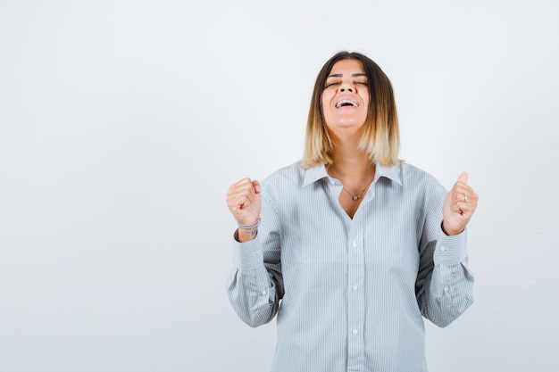 Портрет молодой леди, показывающей жест победителя в негабаритной рубашке и блаженной вид спереди