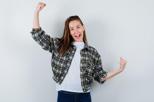 T- 셔츠, 재킷, 청바지에 승자 제스처를 표시하고 행운의 전면보기를 찾고 젊은 아가씨의 초상