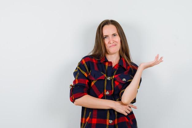 カジュアルなシャツに眉をひそめ、困惑した正面図を見ながら手のひらを横に広げている若い女性の肖像画
