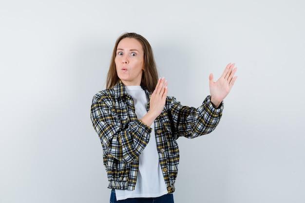 Портрет молодой леди, стоящей в позе боя в футболке, куртке и озадаченно смотрящей спереди