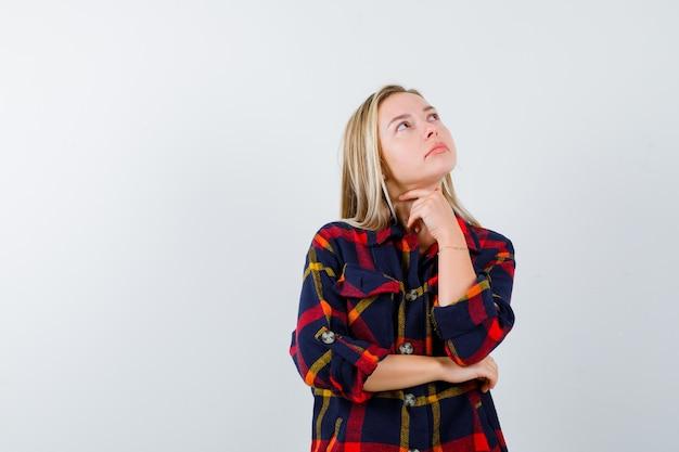 Портрет молодой дамы, стоящей в позе мышления в клетчатой рубашке и задумчивой смотрящей спереди