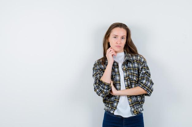 생각에 서있는 젊은 아가씨의 초상 티셔츠, 재킷, 청바지에 포즈를 취하고 사려 깊은 정면보기