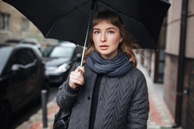 Портрет молодой леди, стоящей на улице с черным зонтиком в руке и задумчиво