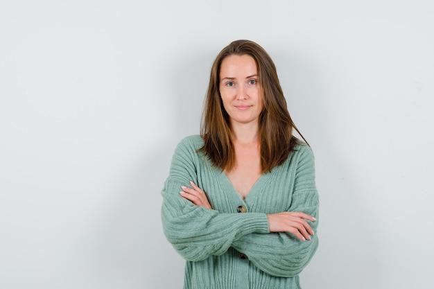 ウールのカーディガンで腕を組んで立って、自信を持って正面を見る若い女性の肖像画