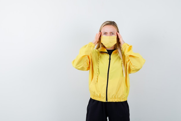トラックスーツ、マスク、疲労感のある正面図で頭痛に苦しんでいる若い女性の肖像画