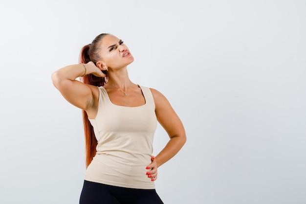 Портрет молодой женщины, страдающей от боли в шее в майке и усталой, вид спереди