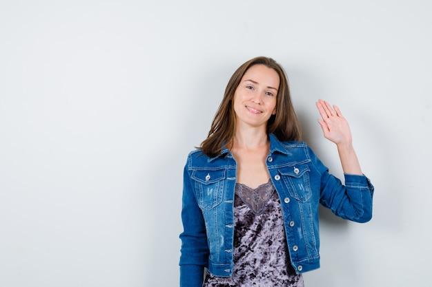 블라우스, 데님 재킷, 귀여운 앞모습을 입고 인사하기 위해 손을 흔드는 젊은 여성의 초상화