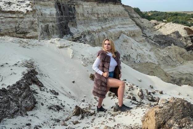 夏の砂岩の近くでポーズをとって毛皮のコートとカジュアルな布で若い女性の肖像画