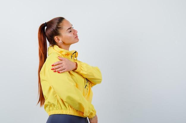 Портрет молодой дамы с рукой на руке, закрывающей глаза в желтой куртке и уверенно выглядящей
