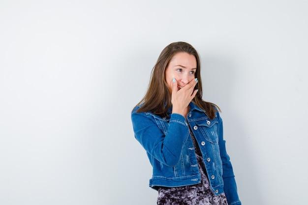 블라우스, 데님 재킷, 쾌활한 전면 보기에 입에 손을 가진 젊은 여자의 초상화