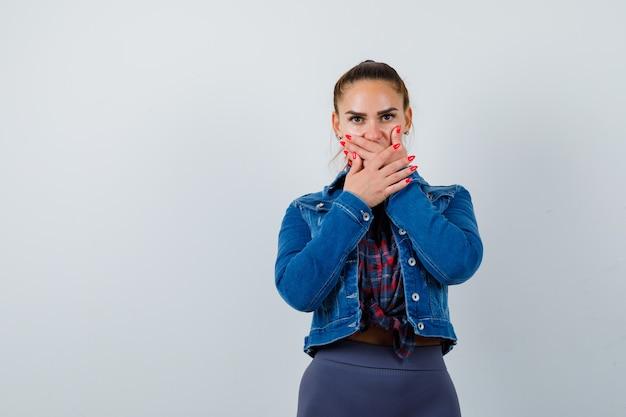 シャツ、ジャケット、怖い正面図で口に手を持っている若い女性の肖像画
