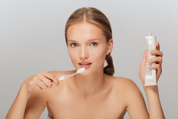 歯磨き粉と歯ブラシを手に持って化粧をせずに若い女性の肖像画