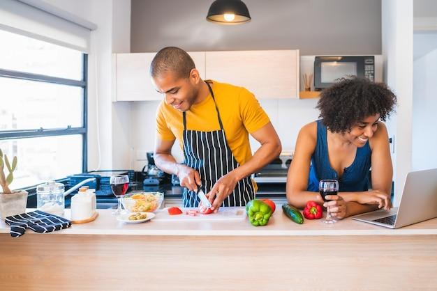 自宅のキッチンで料理をしながらラップトップを使用して若いラテンカップルの肖像画。関係、料理人、ライフスタイルのコンセプト。