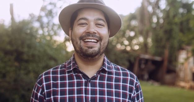 農場の背景にある農場でカジュアルなシャツを着た若いラテン農家の男の肖像画。