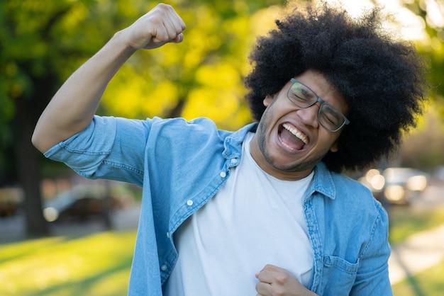 屋外での勝利を祝う若いラテン系男性の肖像画。アーバンコンセプト。成功のコンセプト。