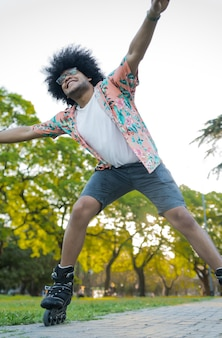 路上で屋外でローラースケートをしながら楽しんでいる若いラテン男性の肖像画。スポーツコンセプト