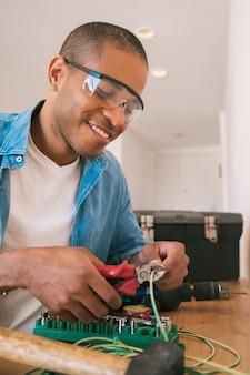 새로운 가정에서 케이블로 전기 문제를 해결하는 젊은 라틴 남자의 초상화. 수리 및 개조 홈 개념.