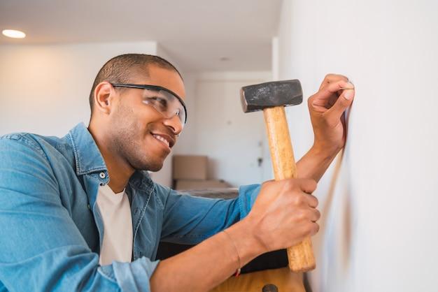 自宅の壁に釘を打つ若いラテン男性の肖像画。住宅改修と修理住宅のコンセプト。