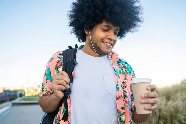 通りを屋外で歩いている間コーヒーを保持している若いラテン男性の肖像画。アーバンコンセプト。