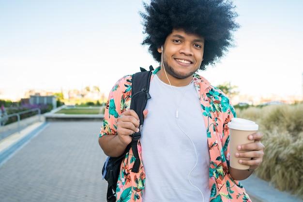 거리에 야외에서 걷는 동안 커피 한 잔을 들고 젊은 라틴 남자의 초상화. 도시 개념.