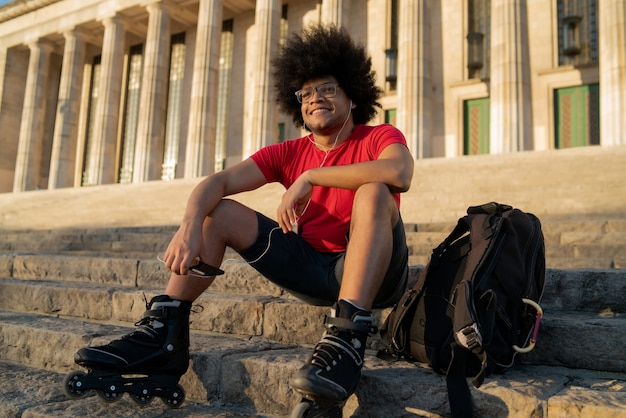 イヤホンで音楽を聴き、屋外に座ってスケートローラーを身に着けている若いラテン男性の肖像画。スポーツの概念。アーバンコンセプト。