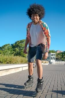 路上で屋外でローラースケートをしている若いラテン系男性の肖像画。スポーツの概念。アーバンコンセプト。