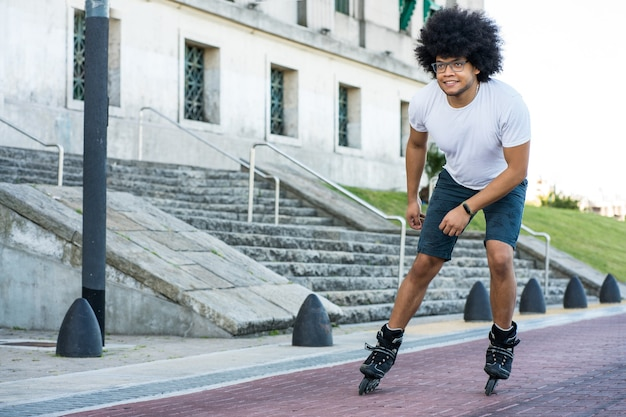 거리에 야외에서 젊은 라틴 남자 rollerskating의 초상화. 스포츠 개념. 도시 개념.