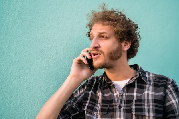 水色の空間に対して電話で話している若いラテン系男性の肖像画。コミュニケーションの概念。