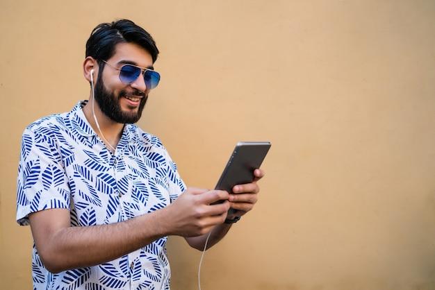 黄色の壁にイヤホンで彼のデジタルタブレットを使用して若いラテン男の肖像画。テクノロジーと都市のコンセプト。