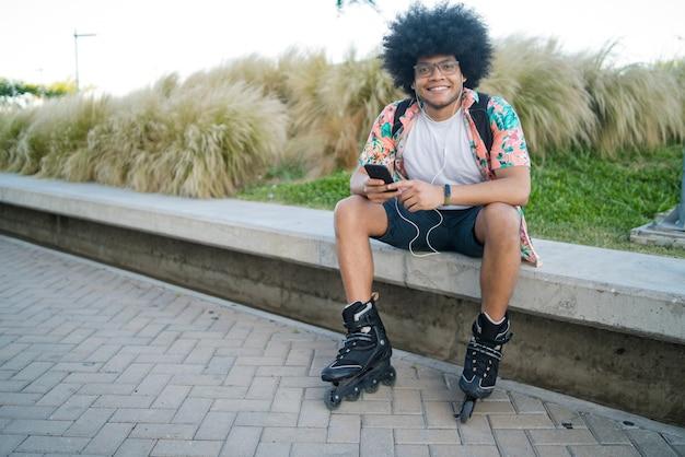 휴대 전화를 사용하고 야외에 앉아 있는 동안 스케이트 롤러를 착용하는 젊은 라틴 남자의 초상화. 스포츠와 도시 개념