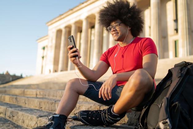 彼の携帯電話を使用し、屋外に座っている間スケートローラーを身に着けている若いラテン系男性の肖像画。スポーツの概念。アーバンコンセプト。