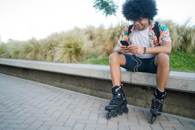 彼の携帯電話を使用して、屋外に座っている間スケートローラーを身に着けている若いラテン系男性の肖像画