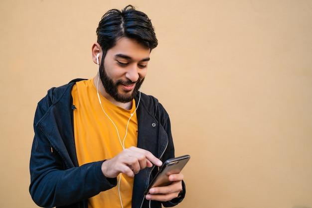 黄色の空間に対してイヤホンで彼の携帯電話を使用して若いラテン男の肖像画。コミュニケーションの概念。