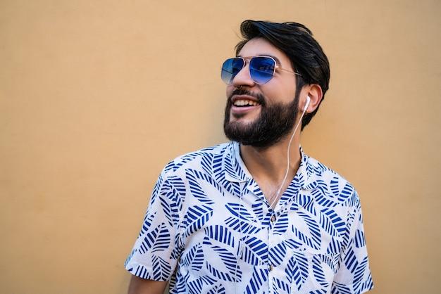 夏服を着て、黄色の背景にイヤホンで音楽を聴いている若いラテン男性の肖像画。