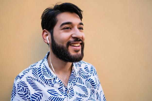 Портрет молодого латинского человека в летней одежде и слушать музыку в наушниках против желтого пространства.