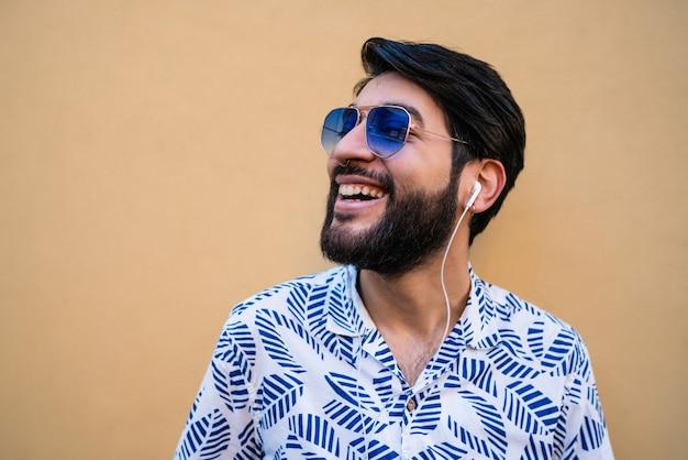 夏服を着て、イヤホンで音楽を聴いている若いラテン系男性の肖像画。