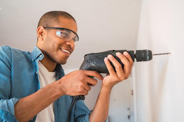 電気ドリルと壁に穴を開ける若いラテン系男性の肖像画。インテリアデザインと住宅リフォームのコンセプト。