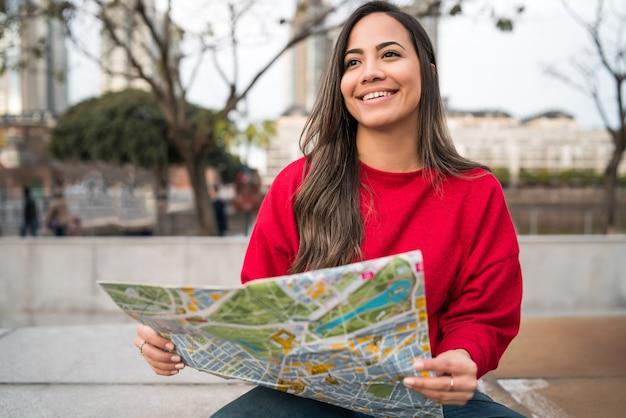 지도를 들고 야외 거리에서 방향을 찾고 젊은 라틴 여자의 초상화. 여행 개념.