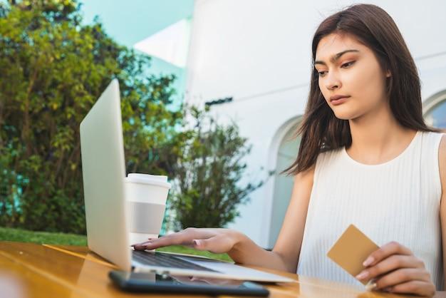 Портрет молодой латинской женщины, держащей кредитную карту и использующей ноутбук для покупок в интернете в кафе. покупки в интернете и концепция образа жизни.