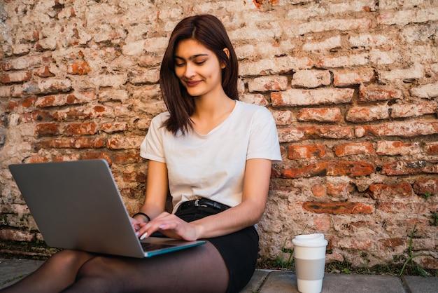 若いラテン女性の肖像画は、レンガの壁に屋外で座っている間、リラックスしてラップトップを使用しています。アーバンコンセプト。