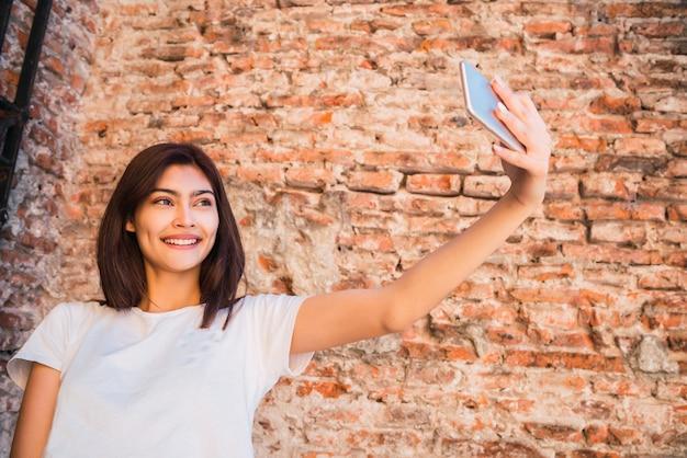 Портрет молодой латинской женщины, делающей селфи со своим мобильным телефоном на открытом воздухе против кирпичной стены. городская концепция.