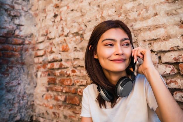 レンガの壁に向かって屋外で電話で話している若いラテン女性の肖像画。都市とコミュニケーションの概念。