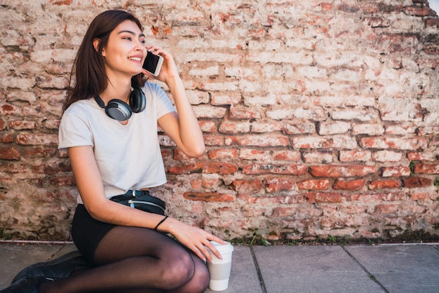 レンガの壁に屋外に座って電話で話している若いラテン女性の肖像画。アーバンコンセプト。